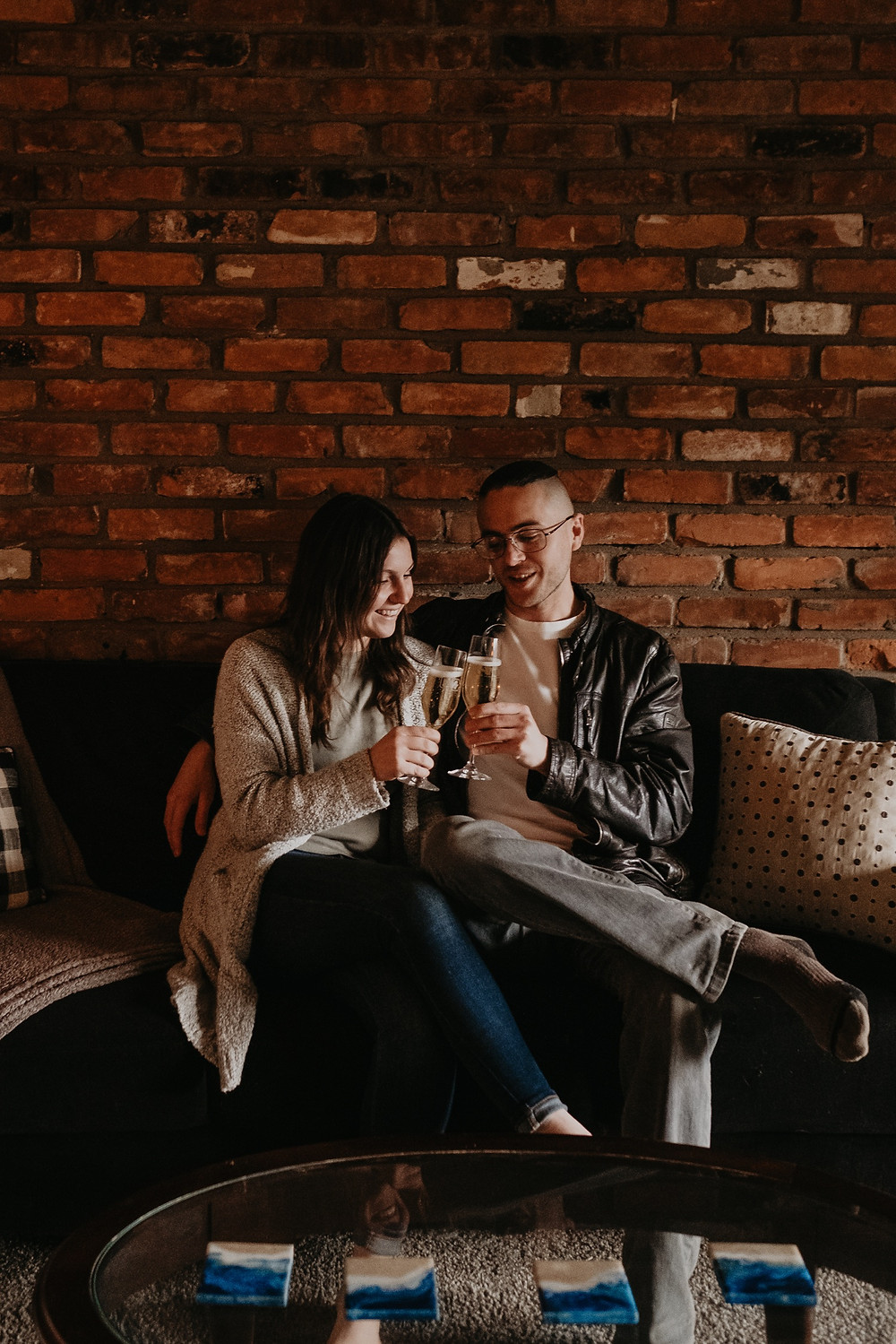 Couple sharing champagne toast on couch at home. Photographed by Nicole Leanne Photography.
