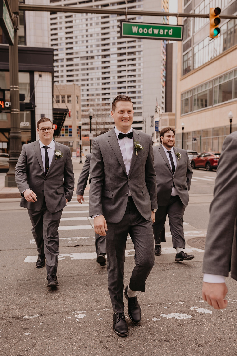 Detroit groom and groomsmen walking across Woodward in Detroit.. Photographed by Nicole Leanne Photography.