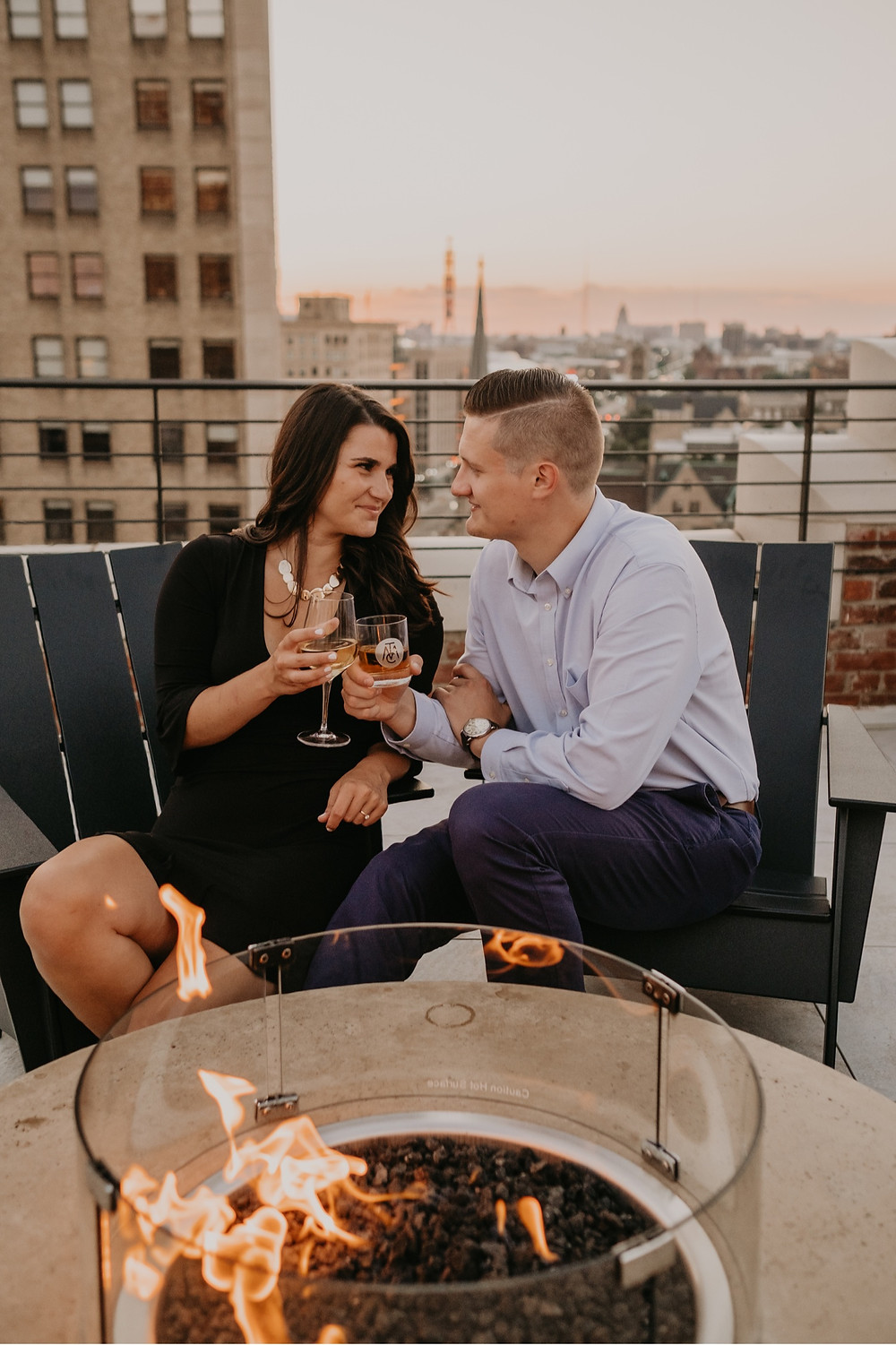 Couple enjoying fire pit on Detroit bar rooftop. Photographed by Nicole Leanne Photography.