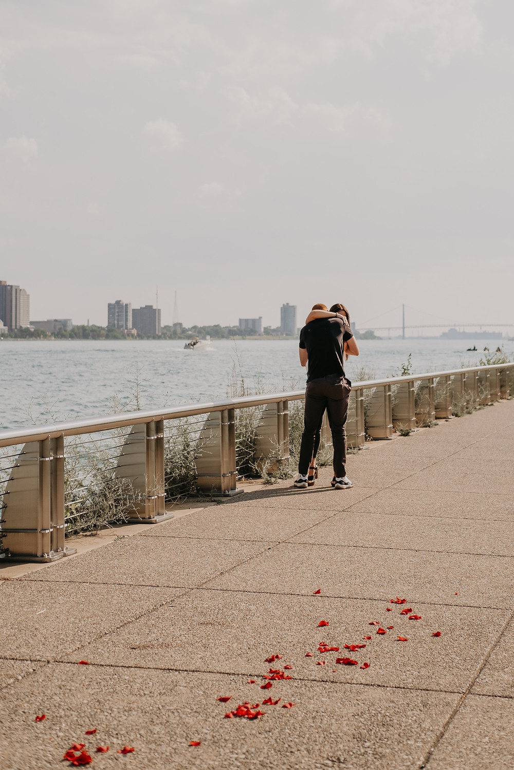 Downtown Detroit proposal with rose petals and river in the background. Photographed by Nicole Leanne Photography
