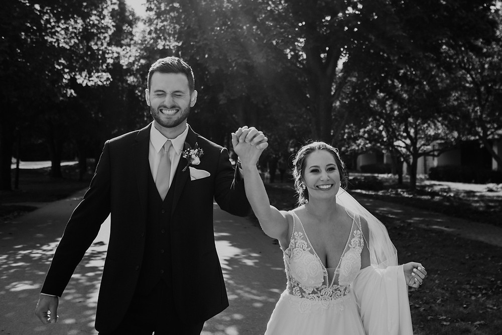 Bride and groom holding hands with big smiles on wedding day after the ceremony. Photography by Nicole Leanne Photography