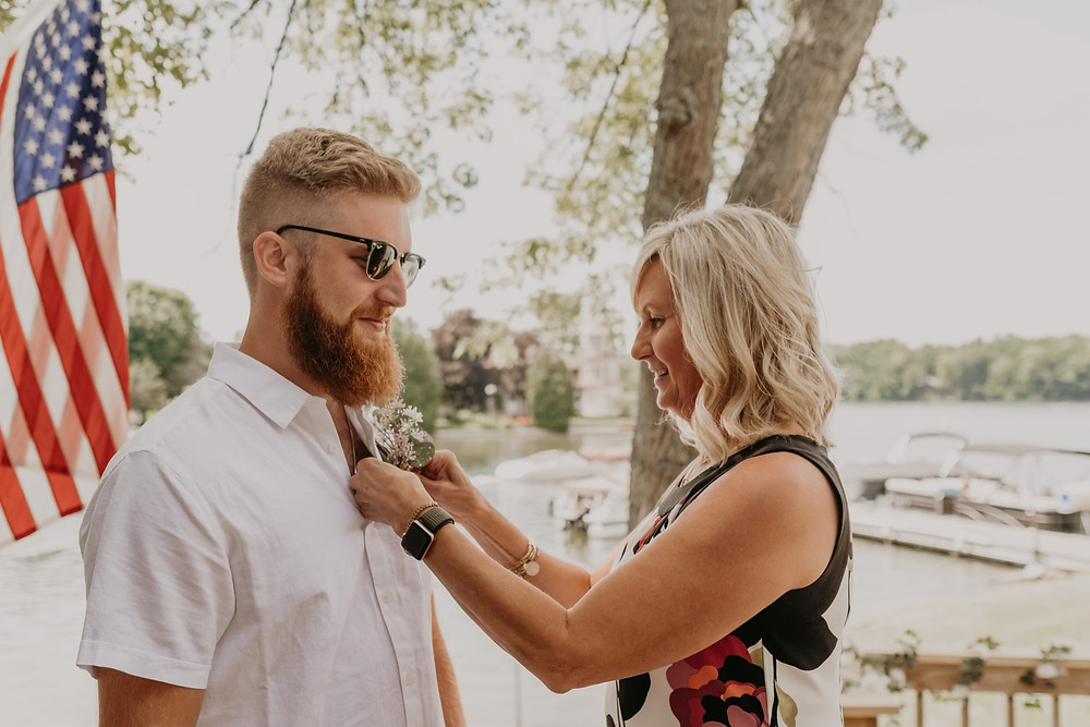 Groom getting boutonniere pinned for wedding ceremony. Photographed by Nicole Leanne Photography.