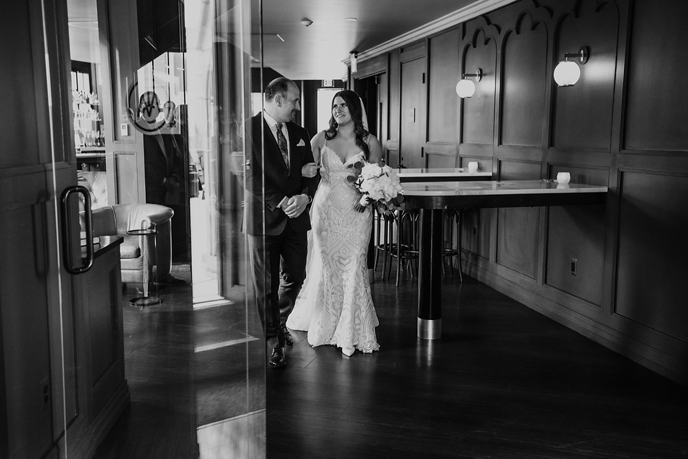 Bride walking to wedding ceremony with father. Photographed by Nicole Leanne Photography.