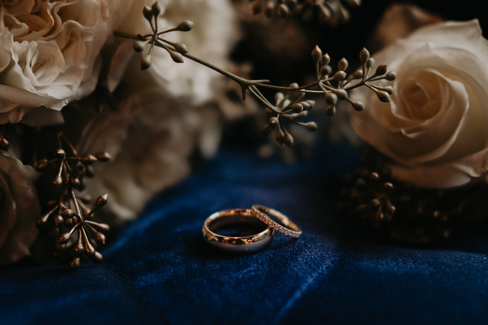 Close up detail shot of wedding rings and florals. Photographed by Nicole Leanne Photography.