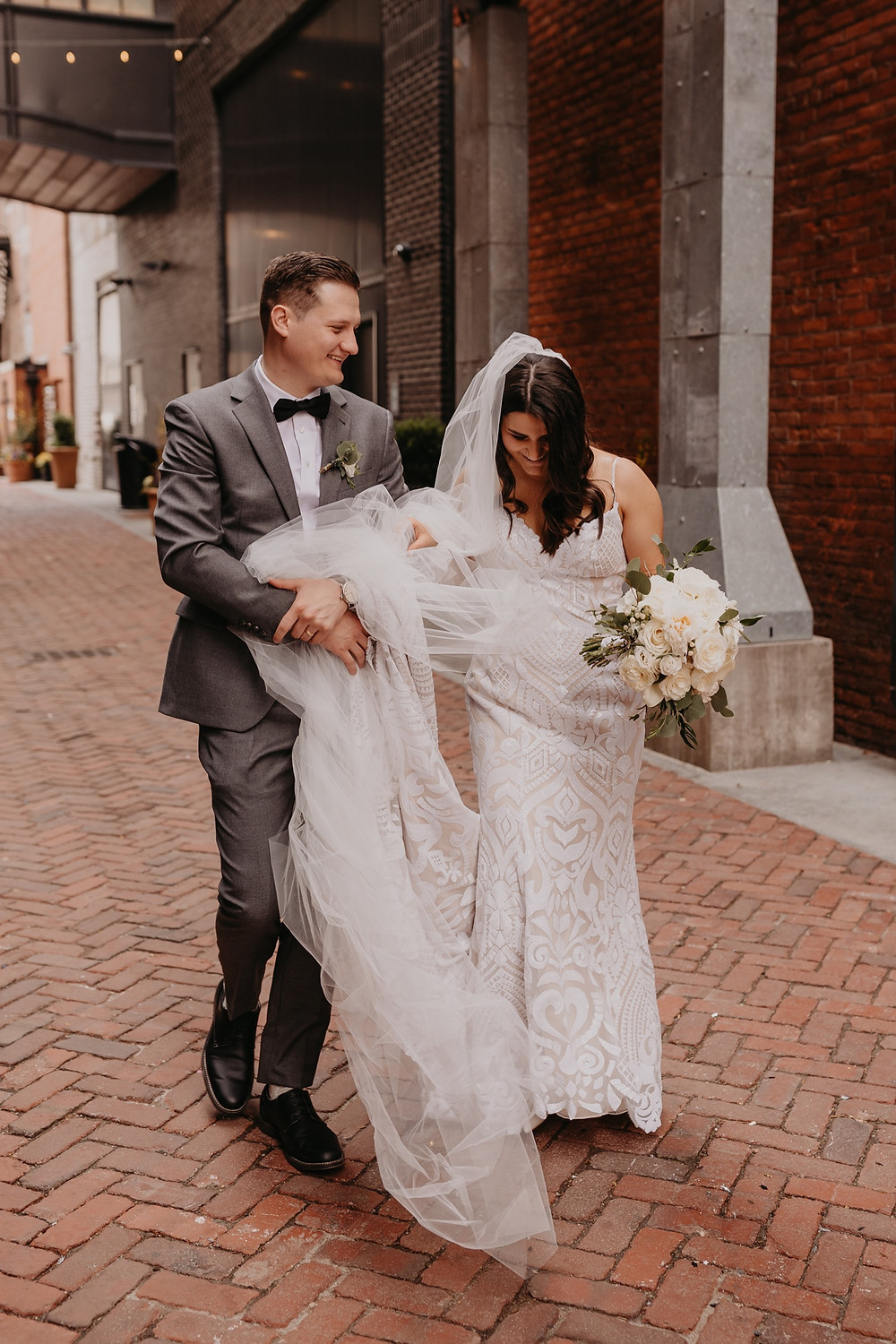 Groom helping hold brides dress and veil in Shinola Alley. Photographed by Nicole Leanne Photography.