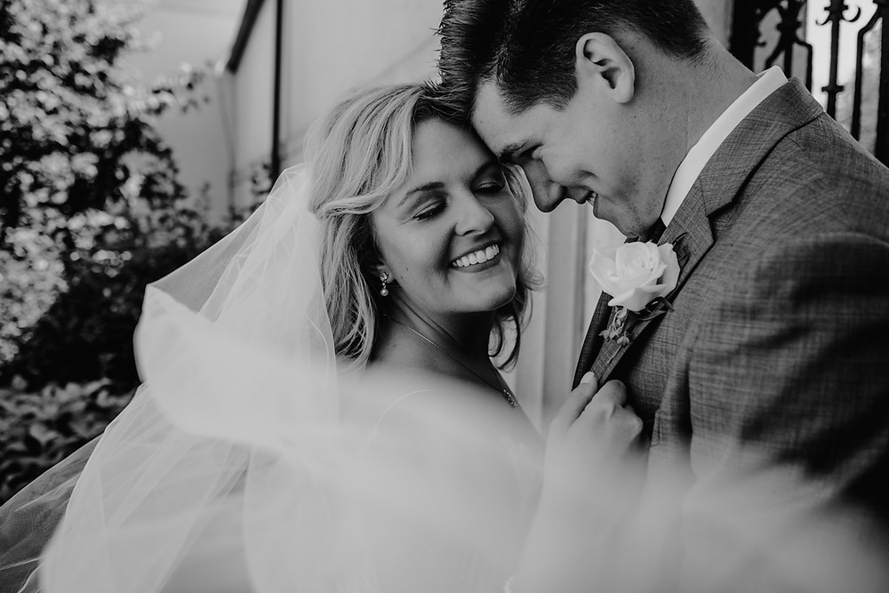 Bride and groom on wedding day with veil blowing in the wind. Photographed by Nicole Leanne Photography