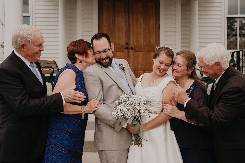 Family congratulating bride and groom after ceremony. Photographed by Nicole Leanne Photography.