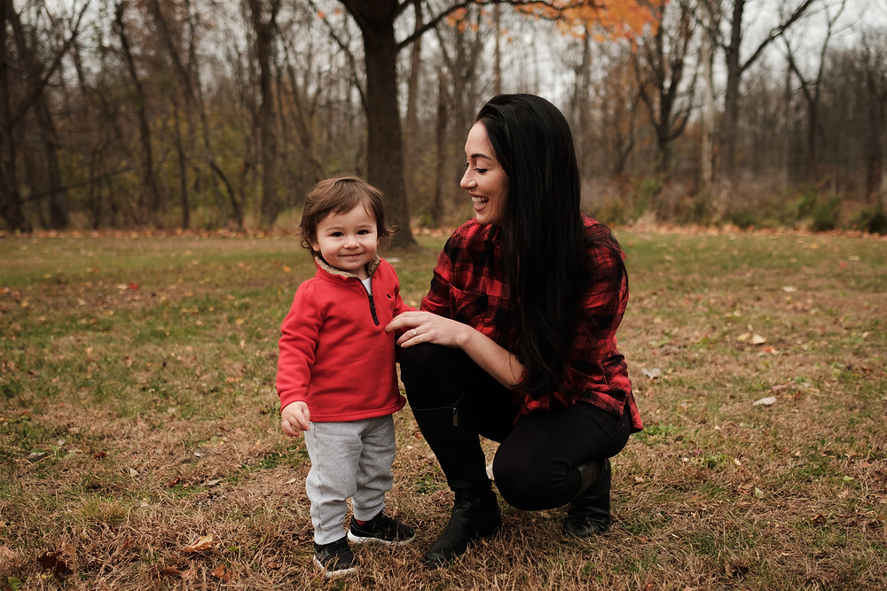 mother laughs with son, fall season