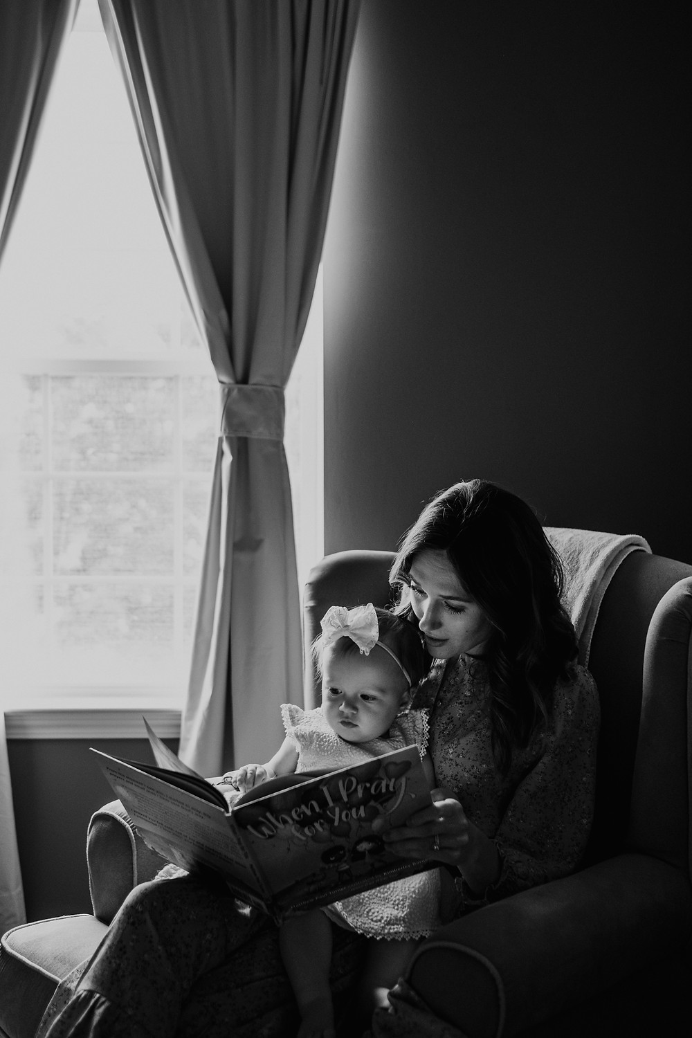 Mother reading book to child on lap. Photographed by Nicole Leanne Photography.