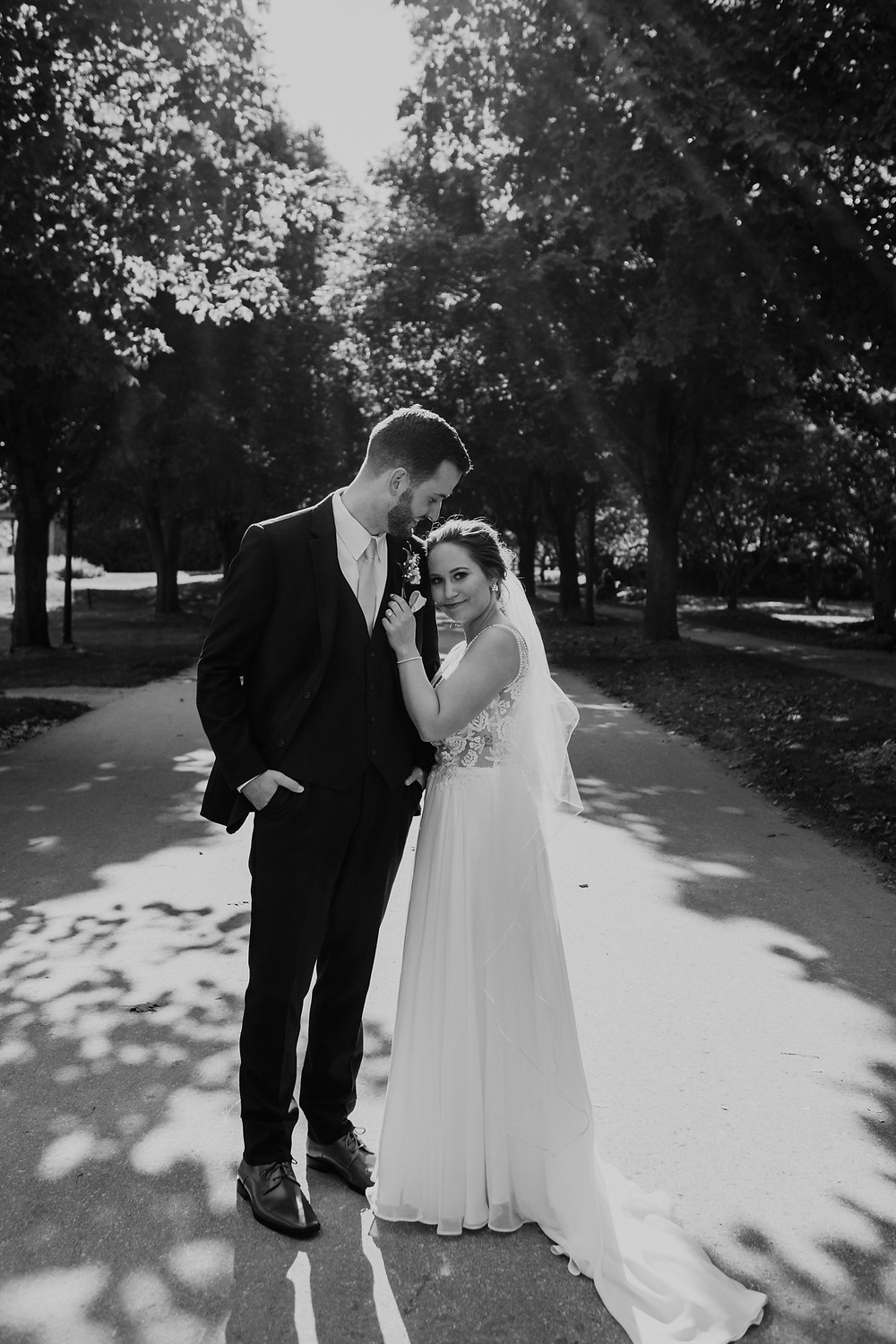 Black and white photo of bride and groom with lots of trees. Photographed by Nicole Leanne Photography.