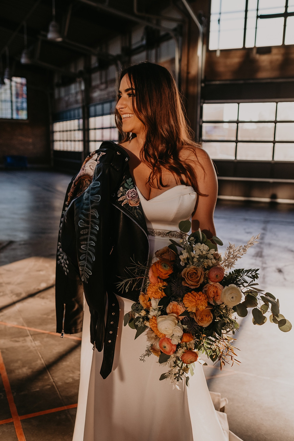 Bride with wedding flowers and leather jacket in Detroit wedding. Photographed by Nicole Leanne Photography.