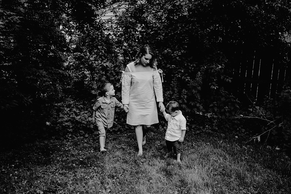 Mother holding children's hands walking through backyard at home. Photographed by Nicole Leanne Photography..