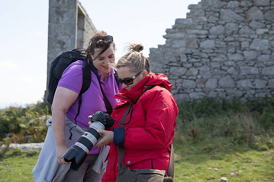 Photography students helping each other on a group photography course on Lundy Island