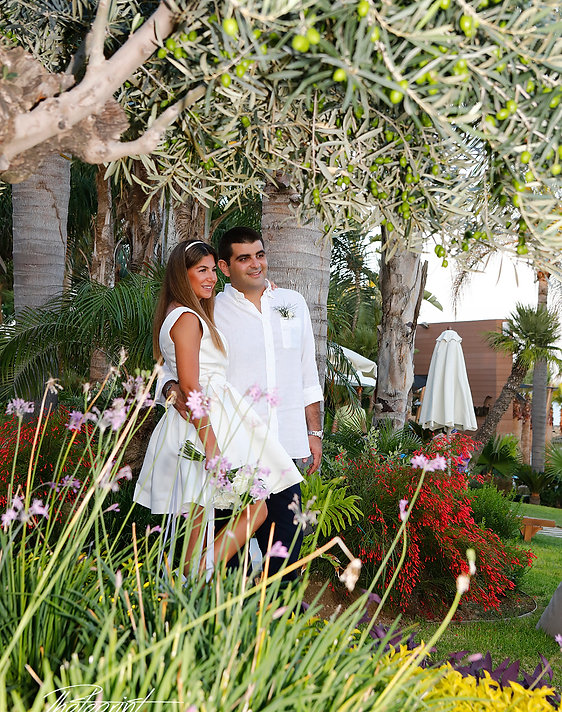 Elegant smiling bride and groom walking on the garden before the wedding at Amathus Beach Hotel in Limassol | photographers in limassol  venues, wedding photography limassol cyprus