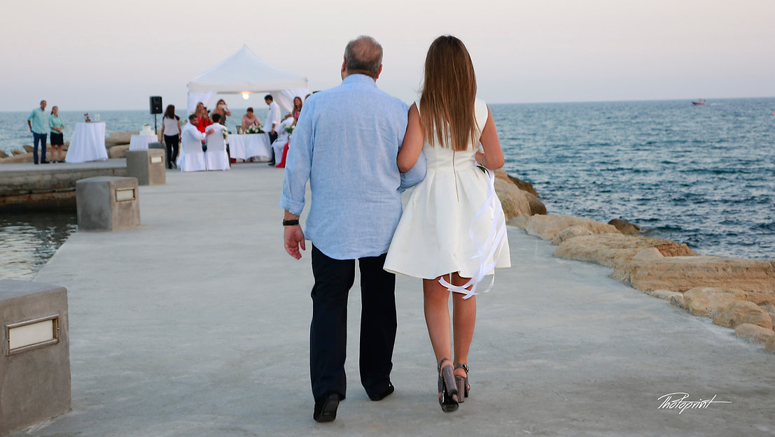 The  bride in a white dress holding a bouquet coming with her father for the wedding ceremony  | wedding limassol photographers cyprus,  best wedding venue limassol