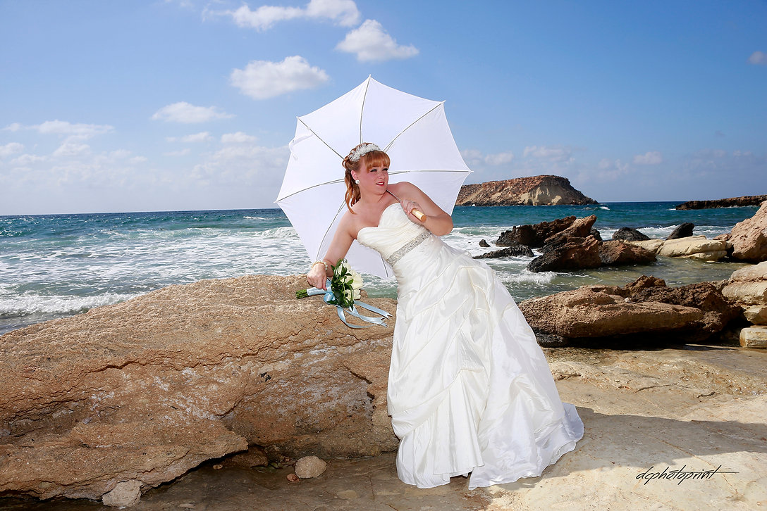 Close-up portrait of gorgeous beautiful bride in white dress with amazing hair style and make up, holding bouquet and  umbrella. Blue Beautiful  Mediterranean Sea on background | photographer in paphos, cyprus sunset images wedding photography paphos