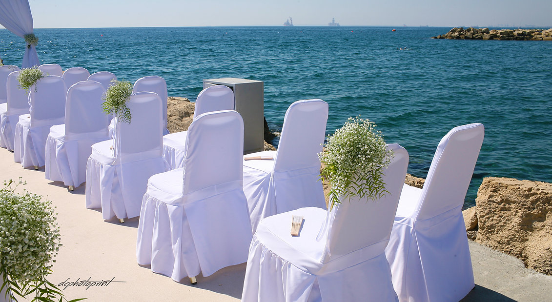 Wedding on the beach of Amathus beach Hotel Limassol, decorated with flowers. Mediterranean Sea on background | wedding photography ideas limassol venues cyprus, wedding venues photographer in limassol cyprus