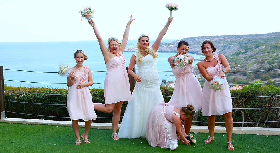Bride with bridesmaids holding bouquets outdoors on the wedding day celebrate.