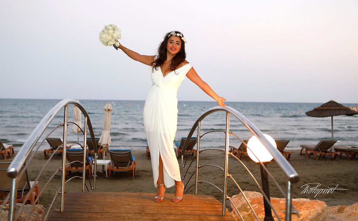 Gorgeous bride in wedding dress with bouquet of flowers posing on the small bridge with a blue sea background | Lebanse weddings in cyprus, wedding photograpgraphers in larnaca cyprus, best wedding Venues for lebanese couple in cyprus, Lebanon photographer backages and prices