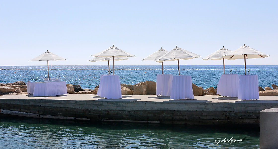tables and umbrellas near the sea ready to celebrate the wedding. Wedding celebration after wewedding | wedding photography ideas limassol venues cyprus,cyprus wedding venues photographers limassol