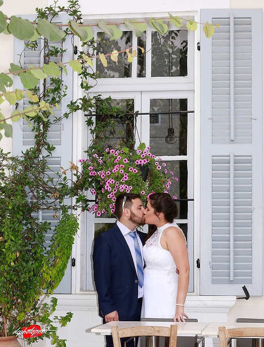 Cheerful married couple standing an old window decorated with Beautiful flowers | cyprus civil wedding photography cost, israeli wedding photography packages cyprus