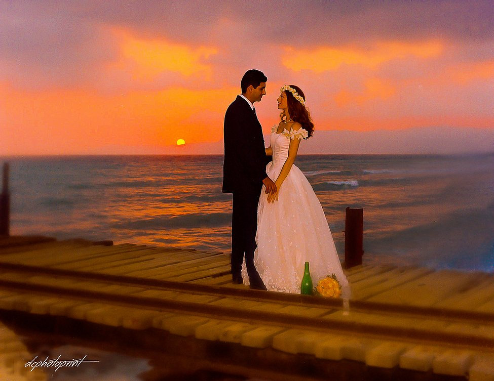 Beautiful and gentle wedding photo session outdoors of the elegant couple on beach at sunset holding hands ( bride in a white dress )