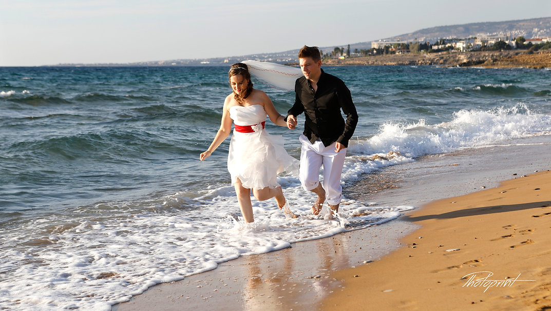 Couple running at lemba beach Paphos holding hands smiling | cyprus wedding hotels paphos,cyprus wedding photos Paphos, cyprus wedding photographer cheap
