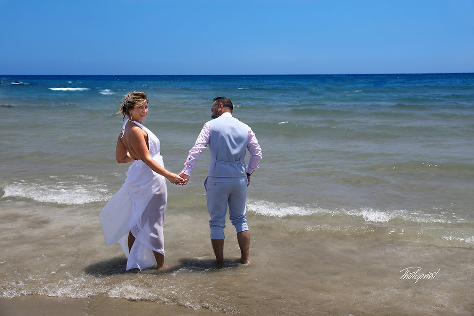 Wedding couple holding hands by the beach at Larnaca.