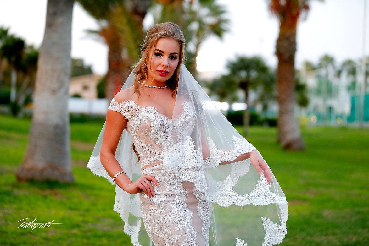 Gorgeous bride in wedding dress with bouquet of flowers posing outdoors in the hotel garden Golden Bey Beach in Larnaca | larnaca wedding photographers in cyprus,lebanese wedding in cyprus,wedding venues in larnaca