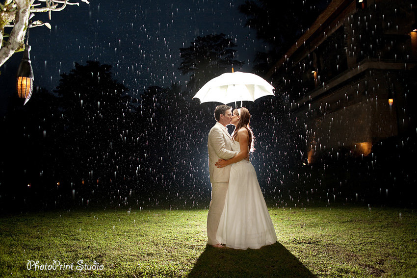 Bride and groom kissing outdoors under rain