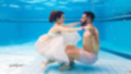 Young couple sitting on the pool underwater holding hands, Kissing | cyprus wedding photos  underwater, professional wedding photo cyprus