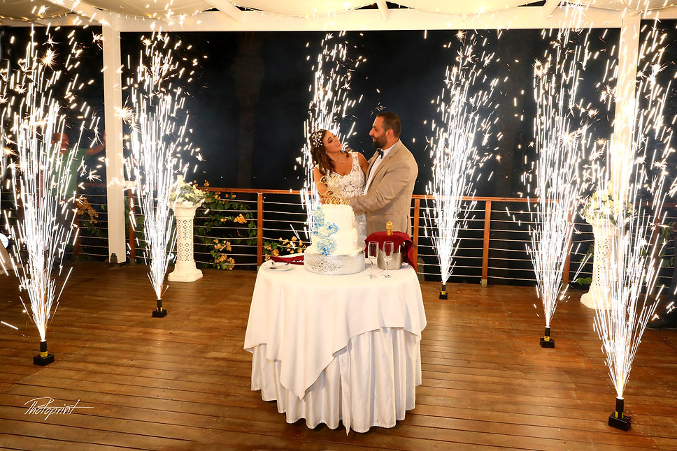 Bride and groom are cutting a wedding cake, fireworks show at the background | getting married in paphos town hall