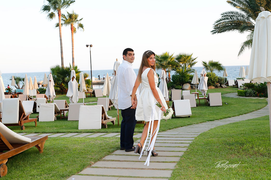 Beautiful and gentle wedding photo session outdoors of the elegant couple going to their wedding through the Amathus  beach Hotel, gardens. Mediterranean Sea on background | Civil Marriage for Lebanese - our clients from abroad, married in limassol municipality cyprus