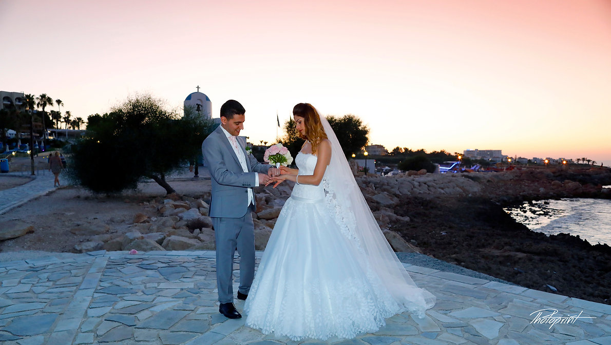 The groom wears the ring bride, at Sunset on a Beautiful Mediterranean Beach at Protaras , cyprus | wedding venues in protaras cyprus, wedding photographer protaras, wedding photography packages cyprus