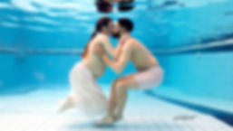 The bride and groom in wedding dresses embrace and kiss underwater at the bottom of a swimming pool | famous wedding photographers Paphos, professional wedding photo in paphos