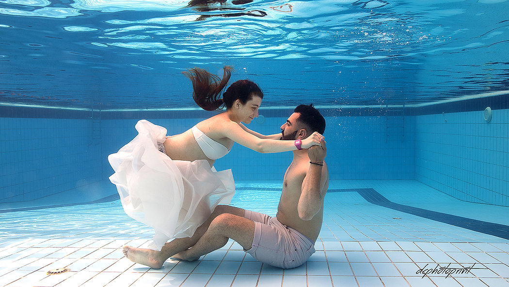 Young couple sitting on the pool underwater holding hands | Paphos wedding photography packages underwater, photography prices cyprus