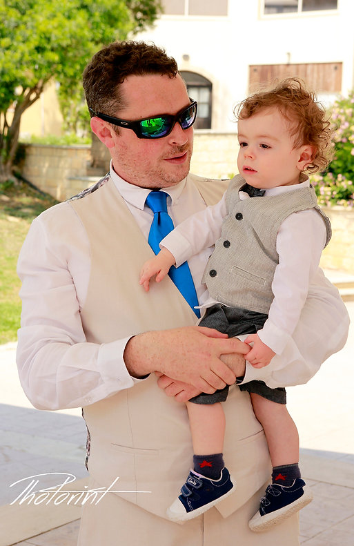 the groom holding their little child are walking towards the white bus | cyprus sunset images wedding photography Geroskipou, best cyprus wedding photographers Geroskipou, wedding photography ideas Geroskipou cyprus