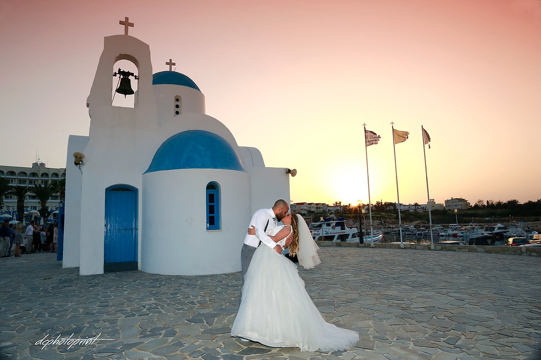 Groom and Bride outdoors Kissing at Sunset in Protaras near St Nicolas church. The magnificent Mediterranean Sea in the background