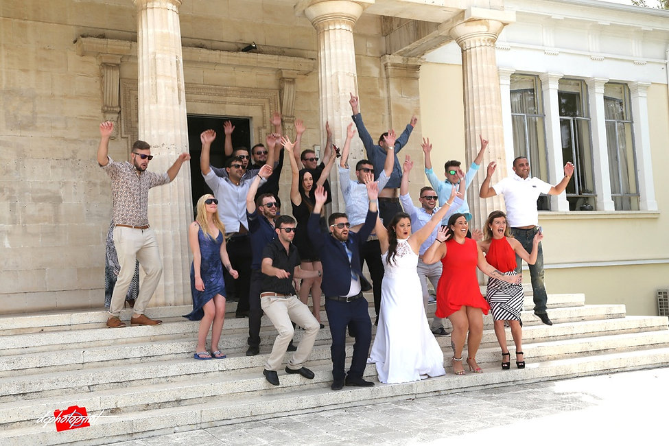 the groom together with other guests who wear sunglasses outside of Town Hall Paphos after the wedding | city hall paphos wedding photography,paphos wedding photographer