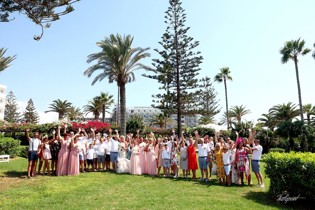 Joe and Ashley and groomsmen with bridesmaids and guests  in sunny day park of  Nissi BeachResort in Ayia Napa after wedding