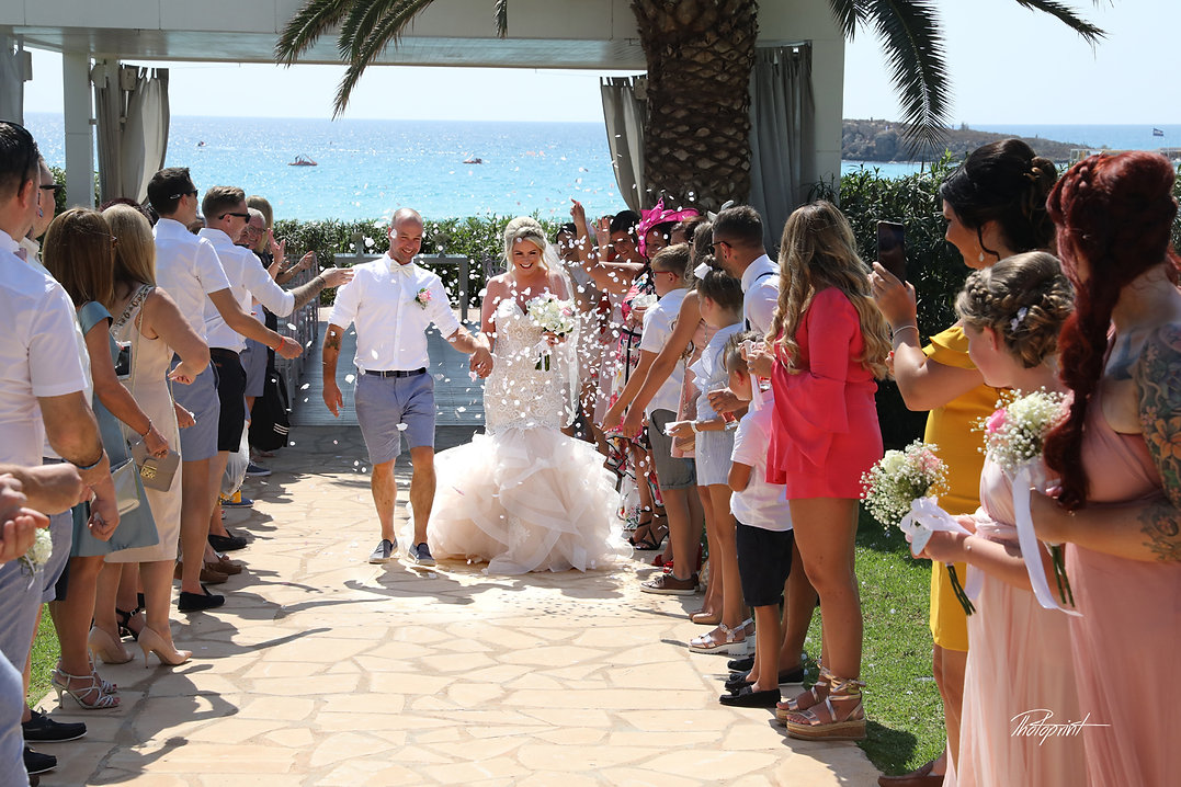 Guests showered newlyweds with colorful confetti after wedding ceremony | ayia napa affordable wedding photography