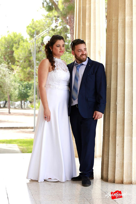 Beautiful israeli couple standing outdoor the town hall Paphos holding hands after the wedding | israeli wedding photographers in limassol, israeli wedding photographer ayia napa