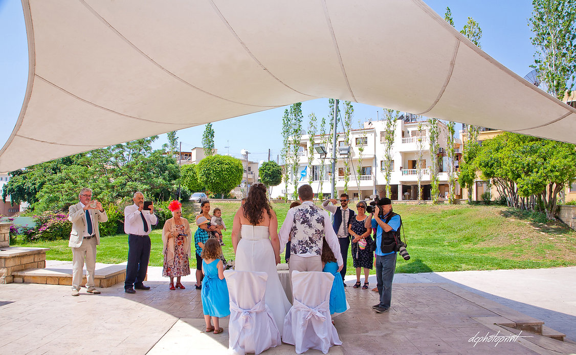 Back view of happy couple during the wedding ceremony | wedding photographer paphos prices, best paphos cyprus wedding photography websites,maried in paphos municipality cyprus