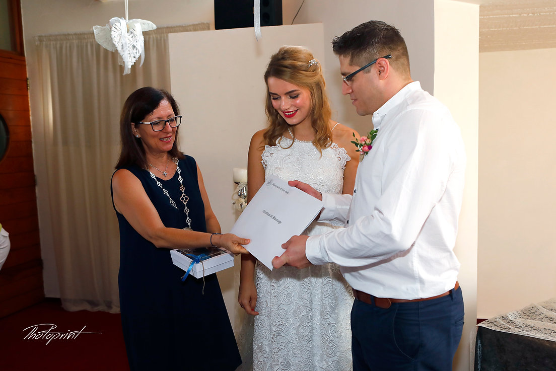 Bride and groom show us the wedding certifigate of marriage after ceremony in ayia napa  | Photography packages for wedding ayia napa, ayia napa wedding photography abroad,cyprus wedding photographers