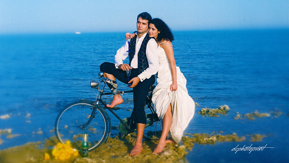 brilliant Picture of elegant beautiful just married romantic couple at Sunset on a beautiful beach of Paphos with their bike.