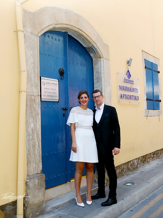 Happy couple standing outside the town hall Larnaca before tha wedding | cyprus sunset images larnaca  wedding photography,photograpfers in larnaca