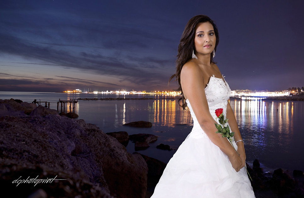 Close-up portrait of gorgeous beautiful bride in white dress with amazing hair style and make up, holding bouquet, Paphos and blue Mediterranean Sea on background at night