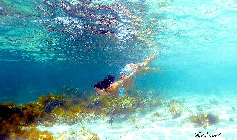Beautiful pregnant bride  swimming underwater in the blue sea  by Nissi Beach at Adams Beach Hotel Ayia Napa.