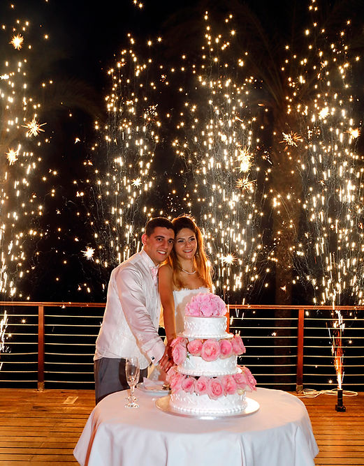 Newly married couple  cutting wedding cake on their wedding party background heavy beautiful fireworks with lots of stars | cyprus wedding photographer ayia napa | wedding portfolio