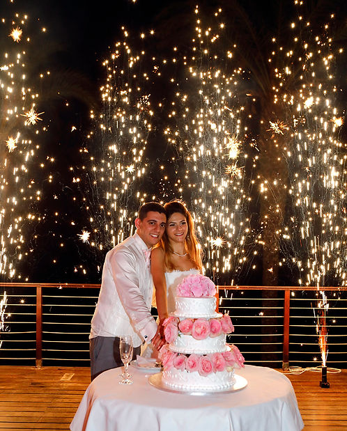 Newly married couple  cutting wedding cake on their wedding party background heavy beautiful fireworks with lots of stars    Beach weddings
